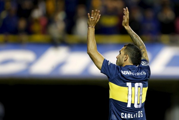 Argentina's Carlos Tevez waves to fans during his presentation as Boca Juniors' new player at La Bombonera stadium in Buenos Aires