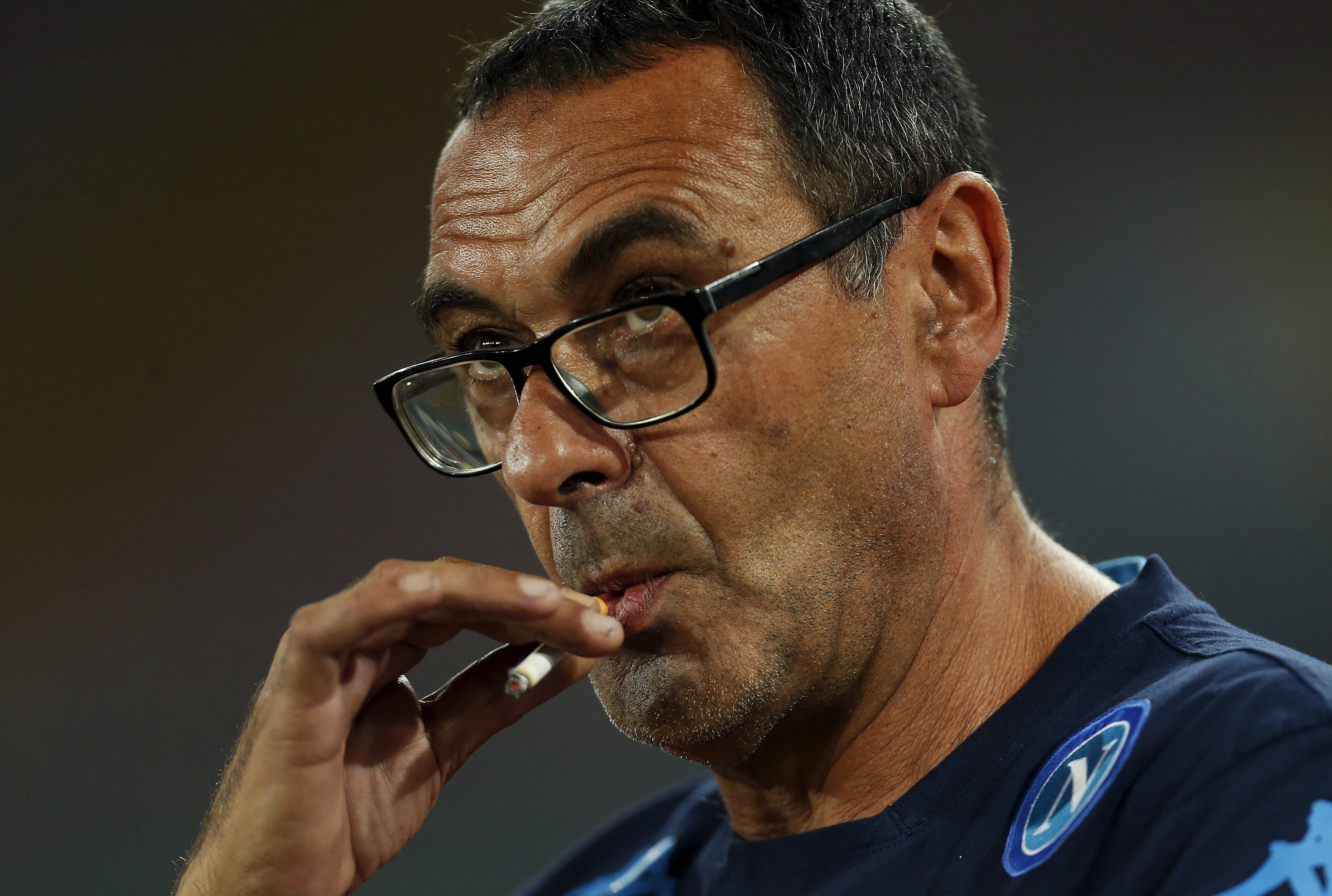 Napoli's coach Maurizio Sarri smokes before to start their Italian Serie A soccer match against Juventus in Naples